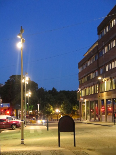 Belysningslösning bestående av bredstrålande LED-armaturer monterade på stolpe och fasad
